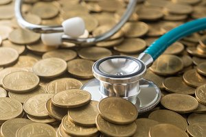 stethoscope on gold coins