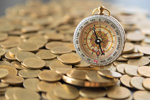 coins money with navigation compass