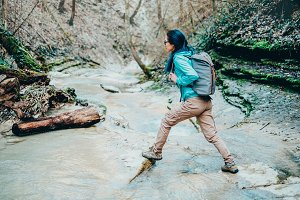 Hiker girl crossing the river