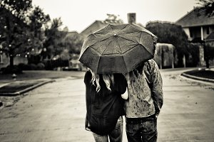 Couple with Umbrella Walking in Rain