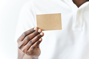 Close up of African man's hands holding business card with copy space for your text or advertising content. Black male wearing white polo shirt showing blank parchment card at the camera. Film effect