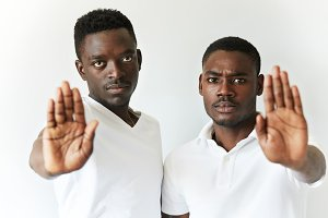 Portrait of two African friends showing stop gesture with their open palms, saying 'stop talking' or 'stay away' to the viewer, looking at the camera with serious expression. Selective focus