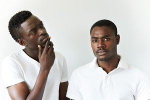 Two African men in casual wear posing isolated against white studio wall. Young black guy looking at the camera with serious expression standing next to his thoughtful friend with a hand on his chin