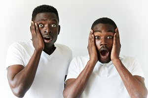 Portrait of two African men looking with shocked expression, with mouth wide open, holding hands on head, watching a football game or viewing latest news, posing isolated against white background