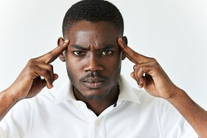 Close up portrait of angry young dark-skinned businessman wearing casual clothes, gesturing with index fingers against his temples: are you crazy? Negative human emotions, facial expressions, feelings