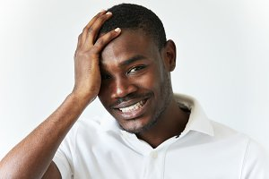 Young handsome African man with healthy skin and short hair-cut, wearing white T-shirt, touching his head, looking at the camera and smiling with confused expression, showing white straight teeth