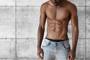Sport and fitness concept. Cropped shot of handsome well-built athletic young African American man in jeans showing his perfect muscular tense abdominal posing shirtless against brick concrete wall