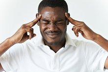 Headshot of dark-skinned man having bad headache, pressing fingers against his temples, suffering from pain. African student or employee closing his eyes, trying to recall something important