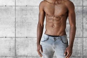 Young dark-skinned model with perfect toned muscular body. Handsome athletic African man in jeans demonstrating his abdominal posing shirtless against gray brick wall. People and lifestyle concept