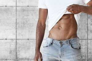 Cropped shot of young African sportsman, undressing, demonstrating his tense abs. Muscular toned fit black male wearing white T-shirt, standing against white copy space wall for your advertisement.
