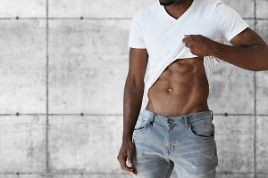 Cropped portrait of young black athlete man wearing jeans and white T-shirt showing off his muscles. Attractive African male undressing and demonstrating his muscular body, against gray brick wall