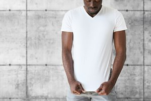 Portrait of handsome young African American student stretching white blank T-shirt with copy space for your text or advertising content, posing against gray brick wall. Lifestyle and people concept