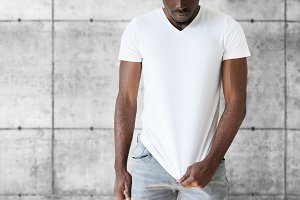 Cropped isolated portrait of athlete African American male model wearing jeans and white blank T-shirt with copy space for your text or promotional content. T-shirt design and advertising concept