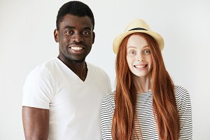 Full face portrait of young couple deliberately smiling at camera in white studio. Red-head girl with hat staring forward with tight and fake smile, Afro American man pretending to smile too.