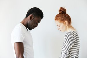 Sad couple looking down with their heads bowed in front of each other. Side view portrait of two sorrowful people: young Caucasian redhead girl and Afro-American melancholic man. Negative emotions.