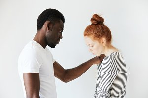 A touching scene of African American man comforting young redhead girl. He put his arm on her shoulder to sympathize her failure and to support her in hard times. Caucasian girl looks down in sorrow.