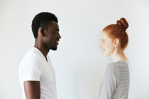 Sideways portrait of a happy couple staring at each other in white morning room. Afro Amercian man in white shirt and redhead girl in stripped longsleeve smiling, showing positive emotions and joy.