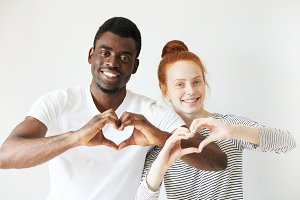 Happy youngsters showing love signs with their hands cupped in heart shape. Afro American man smiling with all his teeth and redhead woman with a bun on her head radiating positive emotions.
