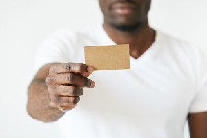 African American man holding a brown empty business card with outstretched arm. He showing this blank cutaway to advertise his services in white room with snowhite background. Closeup studio portrait.