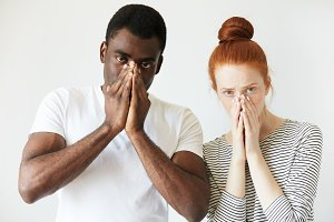 Extraordinary young interracial couple. Caucasian woman in striped top standing next to her African boyfriend looking at the camera with serious expression, covering mouth and nose with both hands