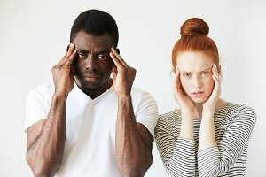 Interracial relationships concept. Black man in white polo shirt and his Caucasian redhead wife, having headache, holding hands on their temples, looking at the camera, exhausted with endless quarrels