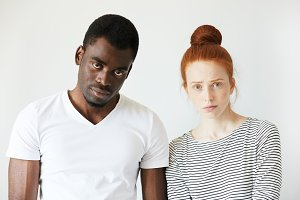 Portrait of young Caucasian female with red hair, angry and disappointed with her African boyfriend, who is standing next to her, looking at the camera with tired expression, fed up with quarrelling