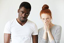 Mixed-race relationships. Interracial couple: Redhead Caucasian woman covering her face and African man in white T-shirt looking at the camera, sorting out their relationships, thinking about divorce.