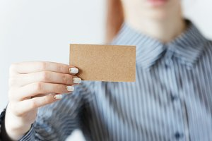 Selective focus. Cropped portrait of female entrepreneur or office worker in striped formal T-shirt and red hair holding a parchment business card with copy space for your text or advertising content