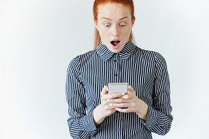Shocking news! Business and technology. Surprised young woman in striped shirt using smart phone. Redhead female office worker holding cell phone with shocked expression while reading a text message