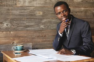 Happy African student in formal suit and glasses looking and smiling at the camera, holding a hand on his chin, doing homework while sitting at the wooden table with cell phone and a cup of coffee