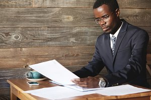 Young African accountant wearing formal wear, holding documents, dealing with paperwork, administrating budget with concentrated look while sitting at the table at a coffee shop. Business and career