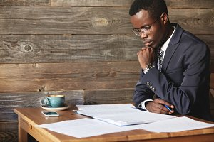 Handsome young African entrepreneur reading a contract before signing it, resting his elbow on the wooden table at a restaurant, sitting with confident concentrated look against wooden wall background
