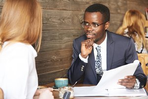 Portrait of African American recruiter in formal wear interviewing redhead Caucasian female applicant, looking and listening attentively, leaning his elbow on wooden table, holding job application