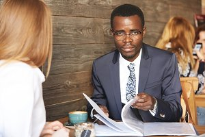 Job interview and employment concept. Portrait of confident African businessman in glasses looking at the camera with serious expression, holding job application while interviewing redhead woman
