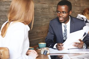 Human resource concept. Portrait of African American HR director wearing formal suit interviewing redhead Caucasian female, checking her resume during a meeting at a coffee shop. Business and career