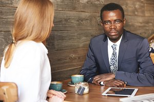 Business communication concept. African American entrepreneur wearing formal suit and glasses, looking at the camera with serious confident expression, while having meeting with his Caucasian partner