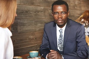 Portrait of confident attractive African businessman in glasses and formal suit looking at the camera, sitting at the table at a coffee while having business lunch with his redhead Caucasian partner