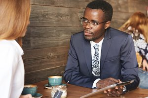 Team work: two corporate workers in formal wear sitting together at the table and discussing business plans. African man using digital tablet during a meeting with his Caucasian female colleague
