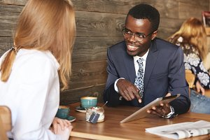 Two business associates of different races having a meeting at a cafe: young African man in formal suit and glasses showing a presentation to his redhead Caucasian female colleague on digital tablet