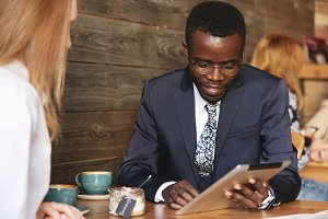 Team work: two business people in formal wear sitting together at the table and discussing something. African man using digital tablet during a business meeting with his Caucasian female partner