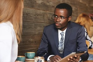 Working on project together. Multiethnic business partners having a conversation at a cafe: African man in glasses holding tablet, listening attentively to his redhead Caucasian female colleague