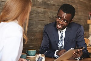 Portrait of young dark-skinned professor in glasses and elegant suit sitting at a coffee shop with his Caucasian student, using tablet for explaining a new material, looking and smiling at the girl