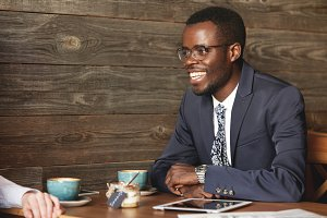 African businessman in formal suit smiling to his job partner discussing collaboration and profit opportunities during coffee meeting at cafe. Entrepreneur has tablet with wireless connection.