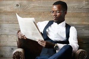 Selective focus. Young African banker wearing formal suit, reading financial newspaper, sitting in leather armchair while waiting in hotel lobby against wooden wall. Success and achievement concept