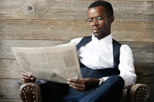 Portrait of young successful confident dark-skinned CEO in elegant suit, busy reading financial news with captured concentrated expression, relaxing in leather armchair. Business and career concept
