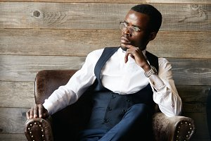 Successful young dark-skinned entrepreneur in formal clothing, sitting in leather armchair against wooden background, thinking and making plans for future, while relaxing after hard day in the office