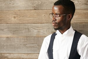 Career and success concept. Portrait of young successful African American businessman or CEO in formal wear and spectacles, looking away with confident expression, thinking of his business plans