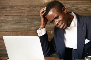 Dark-skinned businessman in formal suit and glasses having stress while working on laptop at the cafe, looking at the screen with stressed and frustrated expression, resting his elbow on the table