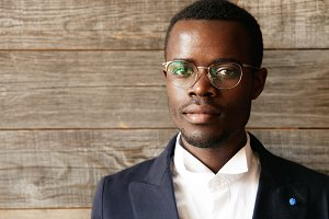 Highly detailed close up portrait of young smart successful African businessman wearing elegant suit and spectacles looking at the camera with serious and confident expression against wooden wall