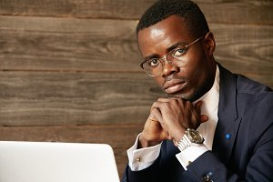 Young African office worker wearing elegant formal wear and glasses while using wireless Internet connection for distant work. Serious black man sitting with crossed hands. looking at the camera